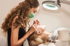 A menina no salão de beleza aumenta o cliente das pestanas O processo de extensão da pestana em um salão de beleza fotografia de stock royalty free