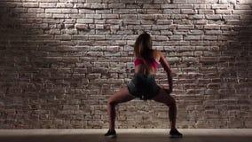 A menina no short da parte superior e da sarja de Nimes da colheita dança o twerk contra uma parede de tijolo Movimento lento filme