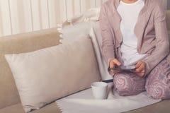 Menina no sofá com uma tabuleta fotos de stock
