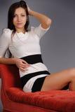 Menina no sofá vermelho Fotografia de Stock Royalty Free
