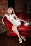 Menina no sofá vermelho Imagens de Stock Royalty Free