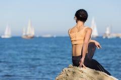 A menina no sportswear observa a regata da vela imagens de stock