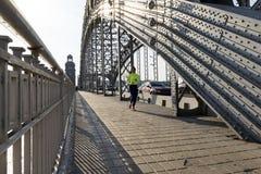 Menina no sportswear que corre na ponte com arcos do metal fotografia de stock royalty free