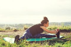 Menina no sportswear que faz esticando o exercício fora foto de stock