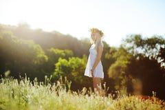 Menina no sundress brancos e uma grinalda das flores em seu aga principal Imagem de Stock