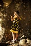 Menina no suporte bonito do vestido pelo jogo enorme da árvore com parte traseira da barra fotografia de stock royalty free