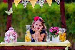 Menina no suporte de limonada Fotografia de Stock
