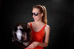 Menina no t-shirt alaranjado com um capacete da motocicleta, óculos de sol, fundo preto Imagens de Stock Royalty Free