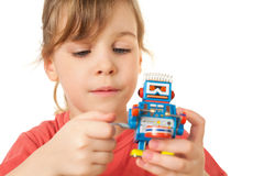 A menina no t-shirt vermelho joga com robô do maquinismo de relojoaria Imagens de Stock