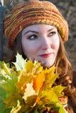 Menina no tampão amarelo com as folhas no outono Fotos de Stock Royalty Free