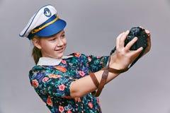 A menina no tampão do capitão faz a câmera do auto fotos de stock