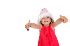 Menina no tampão vermelho do vestido e do Papai Noel do rosa com polegares acima Fotos de Stock Royalty Free