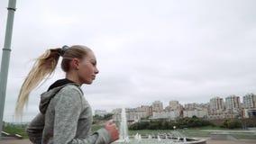 A menina no tempo fresco maçante está correndo O corredor corre abaixo da rua Movimento lento video estoque