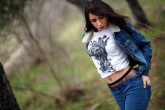 Menina no terno das calças de brim na floresta Fotos de Stock