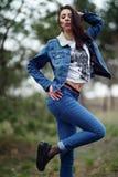 Menina no terno das calças de brim na floresta Fotos de Stock Royalty Free