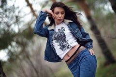 Menina no terno das calças de brim na floresta Imagem de Stock Royalty Free