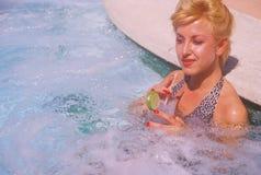 Menina no terno de banho na cuba quente com bebida Imagem de Stock Royalty Free