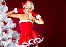 menina no terno de Papai Noel sobre o fundo vermelho Fotografia de Stock Royalty Free