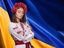 Menina no terno nacional ucraniano contra a bandeira ucraniana Imagens de Stock