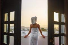 A menina no terraço em uma toalha de banho após o chuveiro olha o por do sol nas montanhas Imagem de Stock Royalty Free