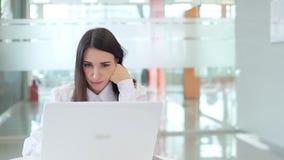 A menina no trabalho no escritório, descontentado porque o portátil não funciona video estoque