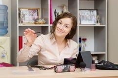 A menina no trabalho no escritório escolhe cosméticos fotos de stock