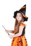 A menina no traje alaranjado da bruxa para o Dia das Bruxas guardara a varinha Imagens de Stock Royalty Free