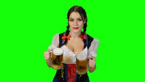 Menina no traje bávaro com vidros de cerveja em suas mãos Tela verde vídeos de arquivo