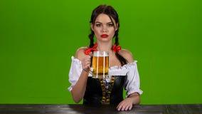 A menina no traje bávaro comemora bebedores de cerveja de Oktoberfest e acenar-los Tela verde vídeos de arquivo