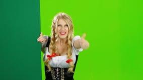 Menina no traje bávaro que acena a mão a ela e que acena adeus Tela verde vídeos de arquivo