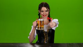 Menina no traje bávaro que sorri e que mostra os polegares acima Tela verde video estoque
