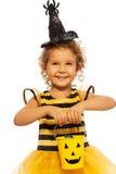 Menina no traje da abelha com cubeta de Dia das Bruxas imagem de stock