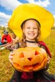 A menina no traje da bruxa guarda a abóbora com mãos imagem de stock