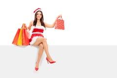 Menina no traje de Santa que guarda sacos de compras Imagem de Stock