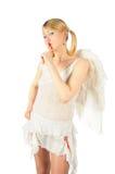 A menina no traje do anjo põr o dedo aos bordos Foto de Stock Royalty Free