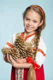 Menina no traje popular do russo que guarda cones do pinho Imagem de Stock Royalty Free