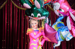 Menina no traje que guarda o grupo dos balões na fase Foto de Stock Royalty Free