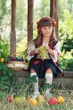 Menina no traje ucraniano nacional que senta-se no jardim com fruto Fotos de Stock
