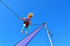 Menina no trampolim do tirante com mola Fotografia de Stock