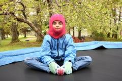 Menina no trampolim na jarda fotos de stock royalty free