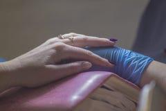 A menina no tratamento de mãos O mestre cobre o polimento do gel do prego Procedimentos cosméticos fotos de stock royalty free