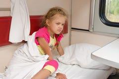 A menina no trem sai sleepily da cama no lugar mais baixo no vagão de segunda classe do compartimento Fotografia de Stock