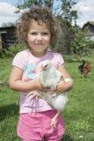 Menina no verão no jardim que guarda uma galinha Imagens de Stock