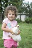 Menina no verão no jardim que guarda uma galinha Foto de Stock Royalty Free