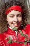 A menina no vermelho olha o botão cheio no parque da mola Foto de Stock