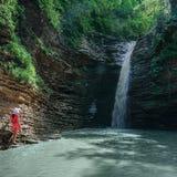 A menina no vermelho olha o cuspe novo da cachoeira no córrego Rufabgo, Adygea, Rússia imagens de stock
