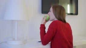 Menina no vermelho que come uma maçã na tabela de funcionamento video estoque