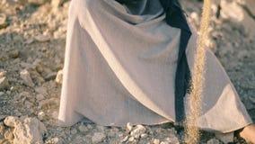 A menina no vestido étnico senta-se perto da estrada e derrama-se a areia fora do jarro A água transformou na areia filme