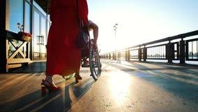 Menina no vestido alaranjado Rolls Guy In uma cadeira de rodas na margem em The Sun vídeos de arquivo
