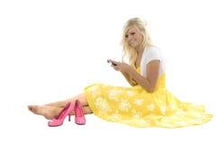 Menina no vestido amarelo que texting sapatas cor-de-rosa fotos de stock royalty free